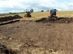 A small digger stripping topsoil into a dumper to be put on spoilheaps