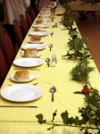 Table decorated with seasonal vegetation and set with cutlery and side plates